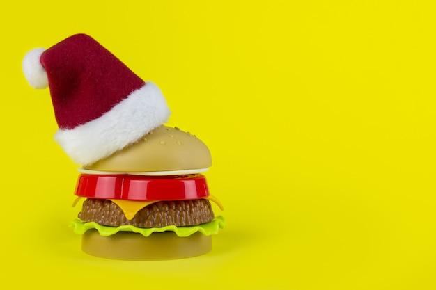 黄色の背景にプラスチックハンバーガークリスマスツリーの赤白サンタ帽子。クリスマスハンバーガー