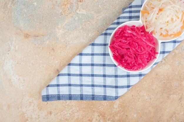 Insalate di crauti rossi e bianchi in ciotole bianche con tovaglia