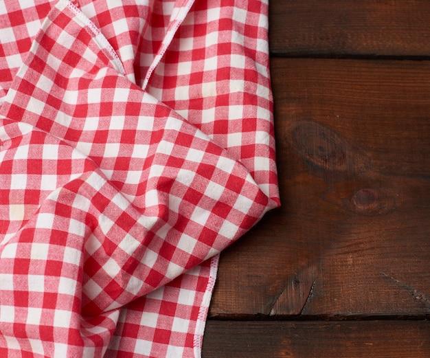 Красно-белое текстильное кухонное полотенце на коричневом деревянном