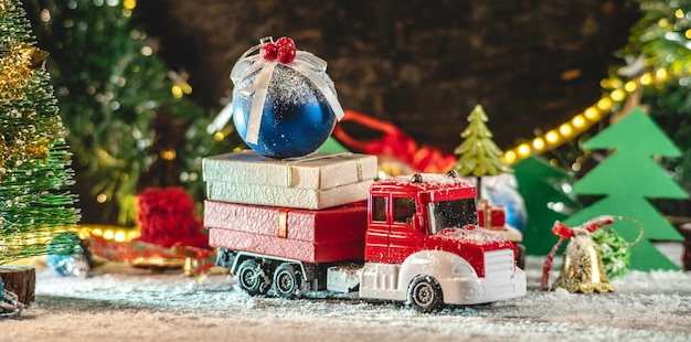 A red and white toy truck is going along a snow covered road carrying gifts