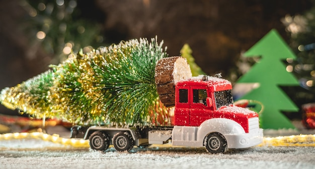 A red and white toy truck is transporting a christmas tree