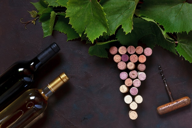 Red and white wine in bottles, corks, corkscrew and grape leaves.