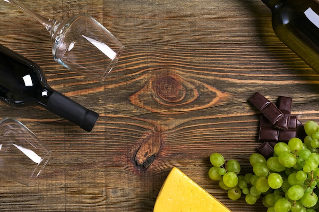 Red and white wine bottles, grape, cheese and glasses over wooden table. top view with copy space. still life. flat lay