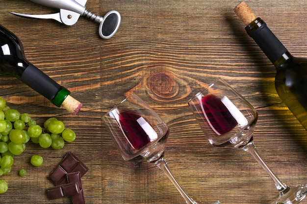 Red and white wine bottles, grape, chocolate and glasses over wooden table. top view with copy space. still life. flat lay