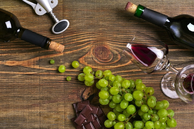 Red and white wine bottles grape chocolate and glasses over wooden table top view with copy space
