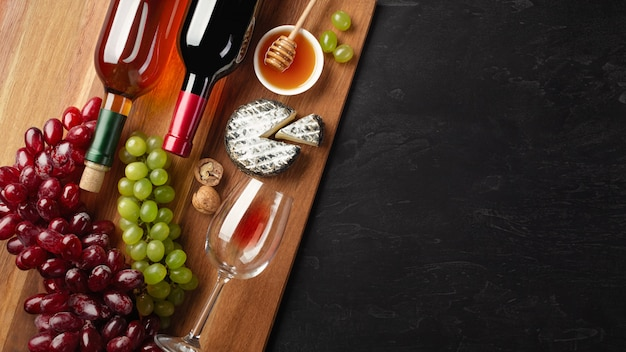 Red and white wine bottles with bunch of grapes, cheese, honey, nuts and wineglass on wood