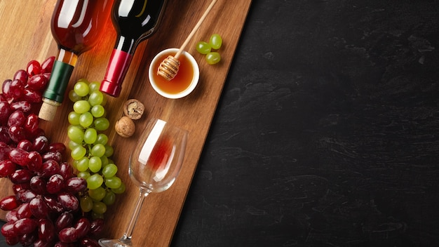 Red and white wine bottles with bunch of grapes, cheese, honey, nuts and wineglass on wooden board and black background. top view with copy space.