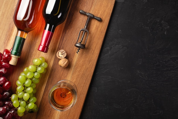 Red and white wine bottles with bunch of grapes, nuts, corkscrew and wineglass on wooden board and black background. top view with copy space.