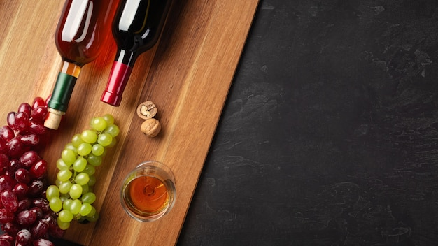 Red and white wine bottles with bunch of grapes, nuts and wineglass on wooden board and black background. top view with copy space.