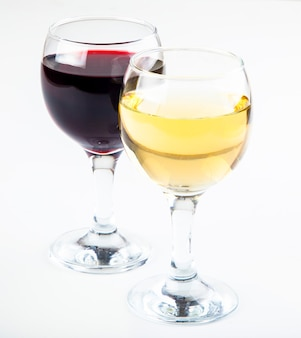 Red and white wine in transparent glasses on a white background