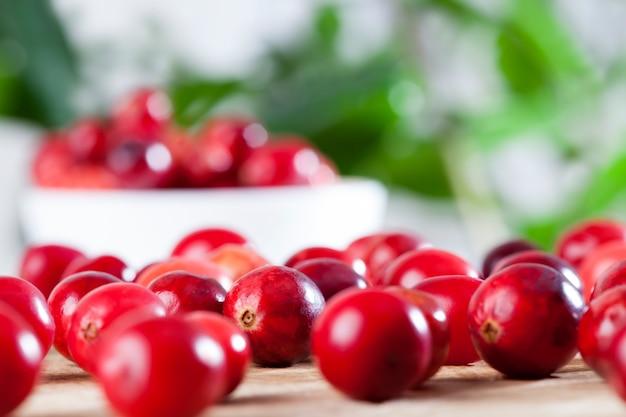 Красная цельная кислая здоровая клюква, красные спелые цельные ягоды клюквы на столе, домашняя клюква, выращенная в промышленном саду