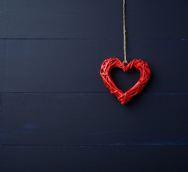 Red wicker decorative heart hanging on brown rope