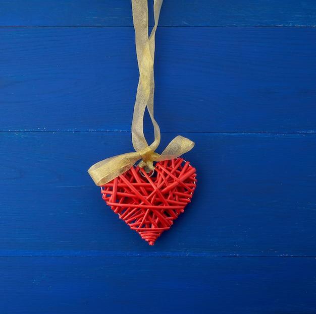 Red wicker decorative heart hanging on silk golden ribbon