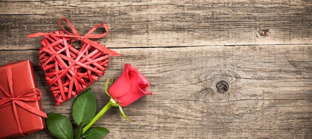 나무 배경에 빨간 고리 버들 세공 심장, 선물 상자 및 장미 꽃