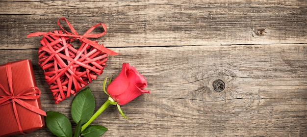 Red wicker heart, gift box and rose flower on wooden background