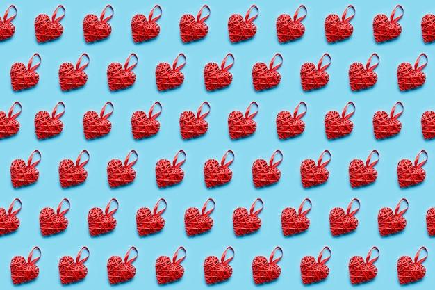 青い背景に赤い籐のハート。シームレスパターン。バレンタインデーのコンセプト、上面図
