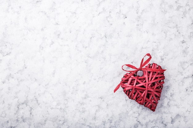 Red wicker heart on snow