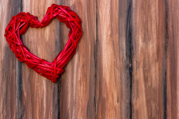 Red wicker heart on a wooden brown  . valentines day, love. copyspace