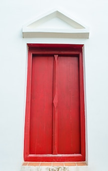 Red window on white wall with gable in temple