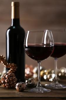 木製の背景の木製テーブルに赤ワインとクリスマスの装飾品
