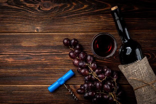 暗い木製の背景に赤ワインとブドウ。