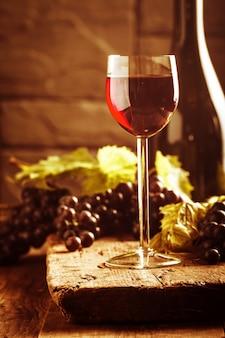 木製のヴィンテージ設定の赤ワインとブドウ