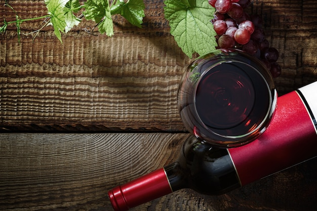 레드 와인과 포도입니다. 유리, 병, 포도, 포도 잎에 있는 레드 와인은 오래된 빈티지 테이블에 있습니다. 평면도.