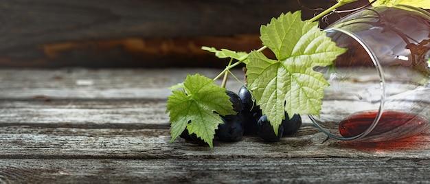 레드 와인과 포도입니다. 나무 테이블에 코르크가 있는 빈티지한 분위기의 와인과 포도. 배너. 텍스트의 공간을 복사합니다.