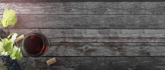레드 와인과 포도입니다. 나무 테이블에 코르크가 있는 빈티지한 분위기의 와인과 포도. 평면도. 배너. 텍스트의 공간을 복사합니다.