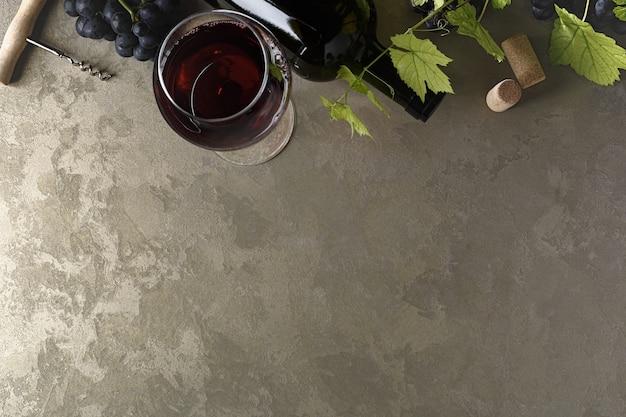 레드 와인과 포도입니다. 나무 테이블에 코르크가 있는 빈티지한 분위기의 와인과 포도. 평면도. 텍스트의 공간을 복사합니다.