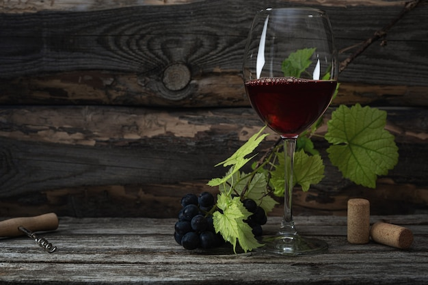 레드 와인과 포도입니다. 나무 테이블에 코르크가 있는 빈티지한 분위기의 와인과 포도.