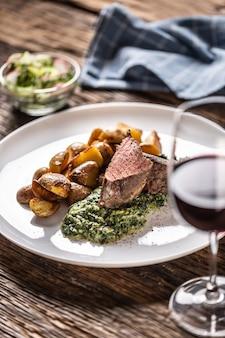 Красное вино в качестве типичного пирожка к стейку су-вид из красного мяса с жареным картофелем, соусом из шпината и свежим салатом, который подается на белой фарфоровой тарелке на деревянном столе.