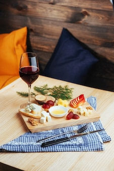Red wine and assorted cheese plate with fruit.