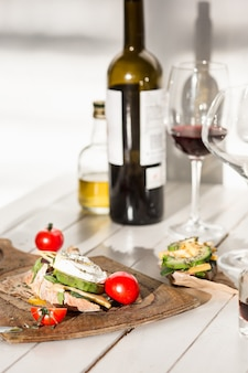 The red wine, baguette and cheese on wooden background
