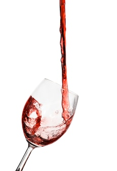 白い背景の上のガラスに注がれている赤ワイン
