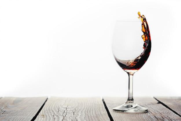 白い背景の上のグラスに注がれている赤ワイン