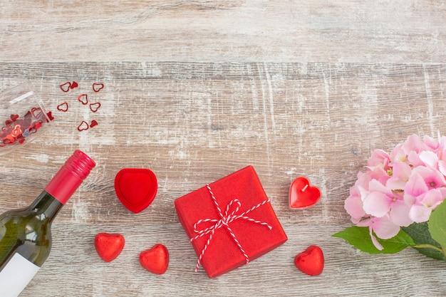 Бутылка красного вина и подарочные коробки, свечи, цветы
