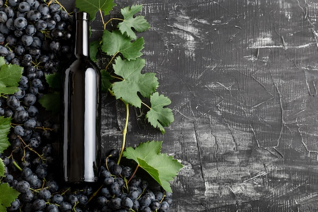 Red wine bottle, black grapes,grape bunches with leaves and vine on dark rustic concrete background with copy space. flat lay wine composition on black stone chalk board table.