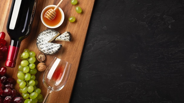 Red wine bottle, bunch of grapes, cheese, honey, ears of wheat and wineglass on wooden board and black background. top view with copy space.