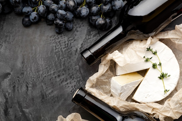 Red wine bottle cheeses grapes. vintage still life wine composition with aged cheese camembert herbs, grapes. restaurant dinner, wine tasting on dark concrete background.