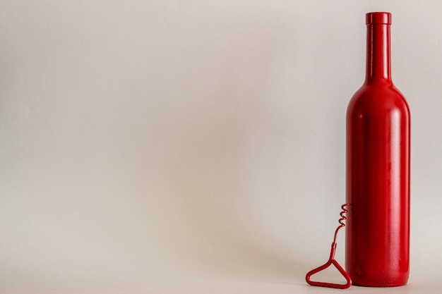Red wine bottle and a corkscrew. gray background. minimalism.