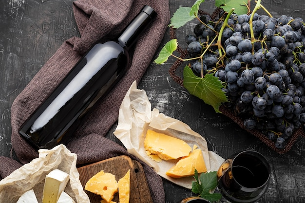 Red wine bottle different cheeses grapes. vintage still life wine composition with camembert aged cheese, grapes. wine drink mockup. restaurant dinner, wine tasting on dark concrete background.