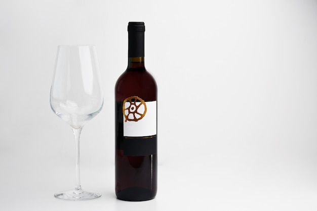 Red wine bottle and glass on white background with copy space for text