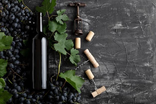 레드 와인 병 포도 뭉치는 어두운 시골풍 콘크리트 배경에 잎과 덩굴 코르크 마개를 꽂습니다. 평평한 평신도 와인 구성 레드 와인 병은 복사 공간이 있는 검은 돌 테이블에 있습니다.