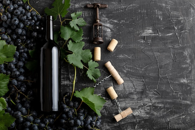 Red wine bottle grape bunches with leaves and vines corkscrew on dark rustic concrete background. flat lay wine composition red wine bottle on black stone table with copy space.