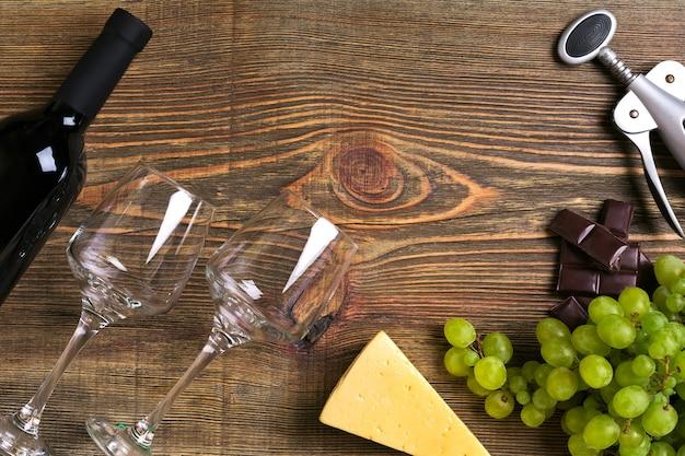 木製のテーブルの上に赤ワインのボトル、ブドウ、チーズ、グラス。コピースペースのある上面図。静物。フラットレイ