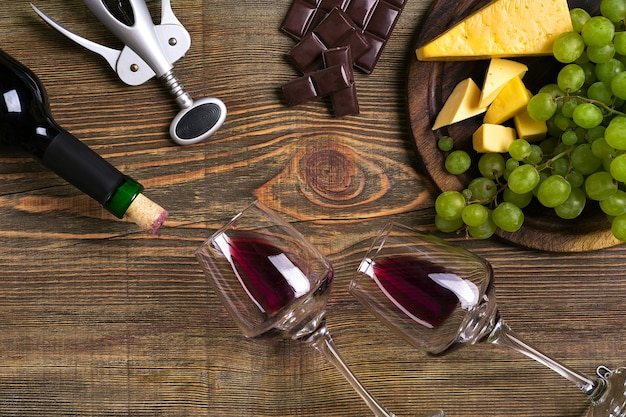 Red wine bottle, grape, cheese and glasses over wooden table. top view with copy space. still life. flat lay