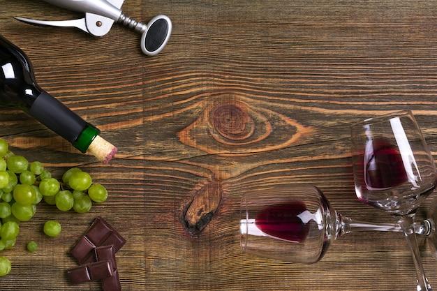 木製のテーブルの上に赤ワインのボトル、ブドウ、チョコレート、グラス。コピースペースのある上面図。静物。フラットレイ