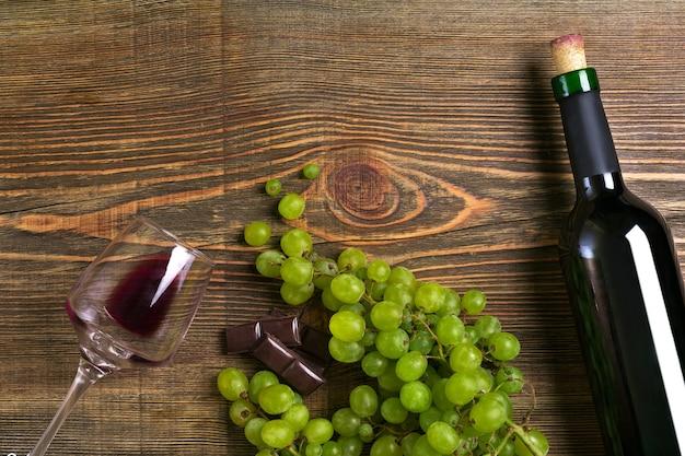 Бутылка красного вина, виноградный шоколад и бокалы над деревянным столом с копией пространства
