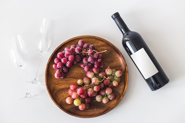 Red wine bottle, large burgundy fresh grapes on round wooden dish, empty wine glasses on white wall, copy space flat lay, top view.